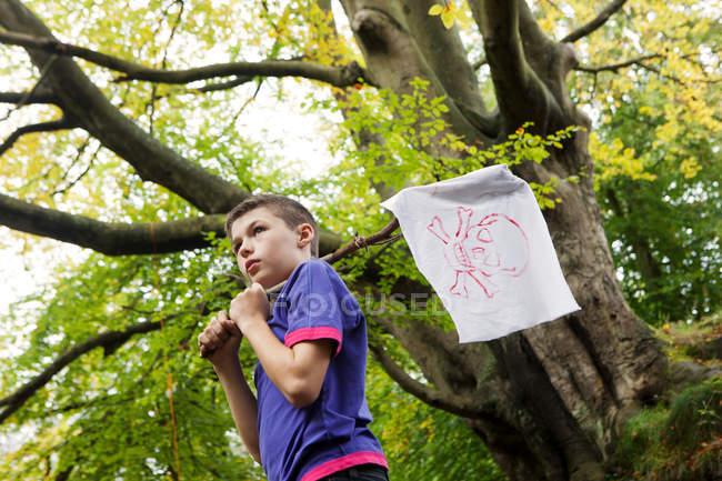 Niño sosteniendo una bandera pirata - foto de stock