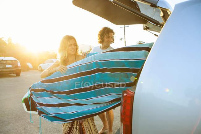 Casal tomando pranchas de surf da bota do carro — Fotografia de Stock