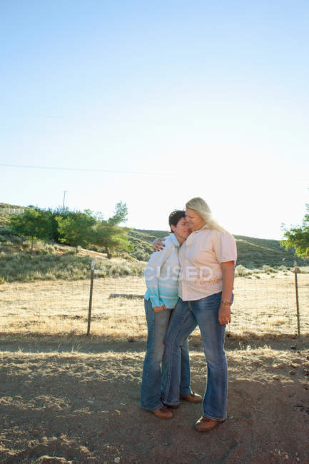 Mature lesbian couple embracing on ranch — Stock Photo