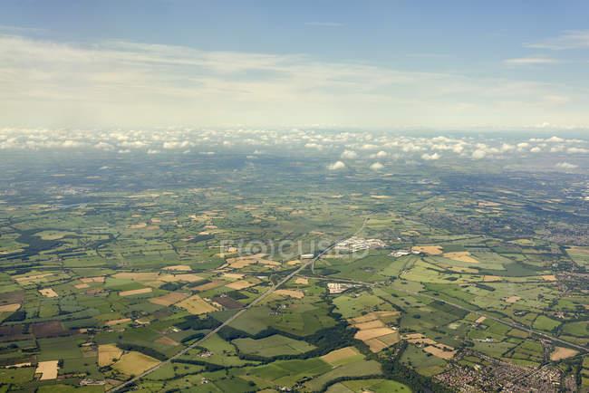Vista aérea de los campos y el paisaje nublado a la luz del sol - foto de stock