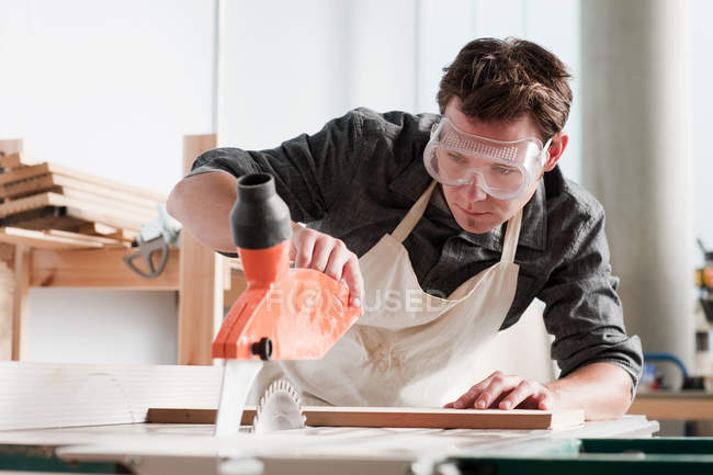 Male carpenter using saw in workshop — Stock Photo