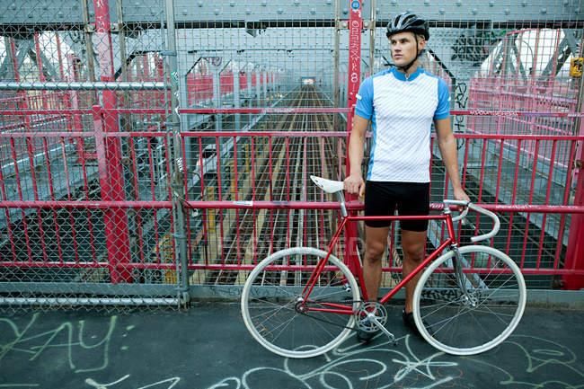 Cycliste debout sur le pont avec vélo, Brooklyn, Etats-Unis — Photo de stock