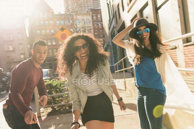 Portrait of three mid adult fooling around on city street — Stock Photo