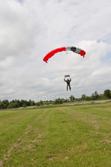 Парашютист, посадка с парашютом на лугу — стоковое фото