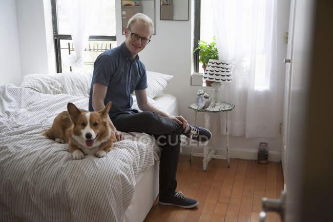 Corgi bonito cão deitado na cama vigiado pelo jovem — Fotografia de Stock