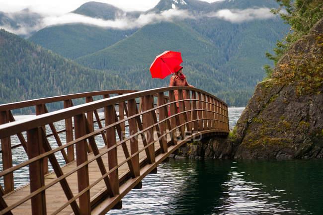 Woman with umbrella on wooden bridge — Stock Photo