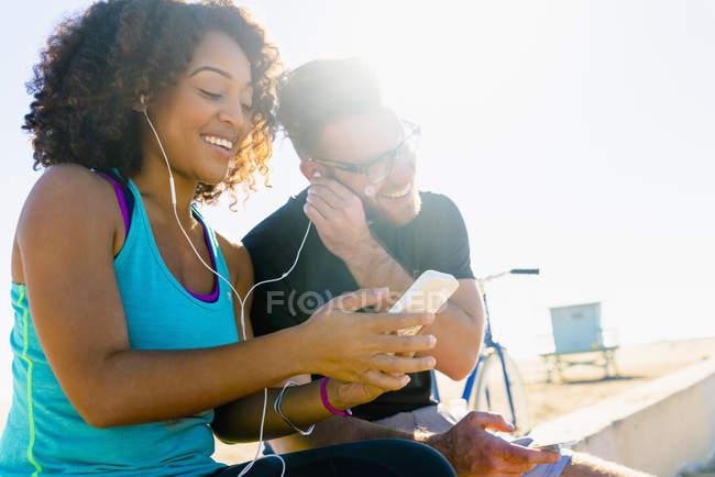 Coppia seduta sul muro, condivisione di auricolari, ascolto di musica, utilizzando smartphone — Foto stock