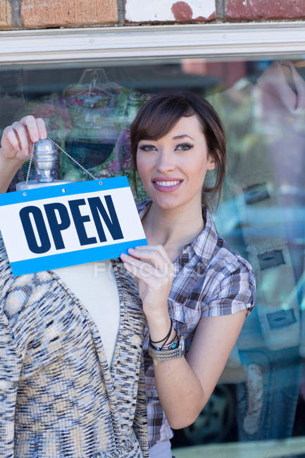 Woman hanging open sign on mannequin — Stock Photo