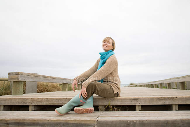 Mulher sentada na passarela na costa — Fotografia de Stock
