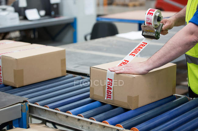 Man packing cardboard box with tape in warehouse — Stock Photo