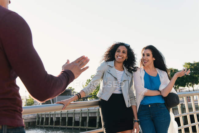 Two mid adult women greeting male friend on waterfront — Stock Photo
