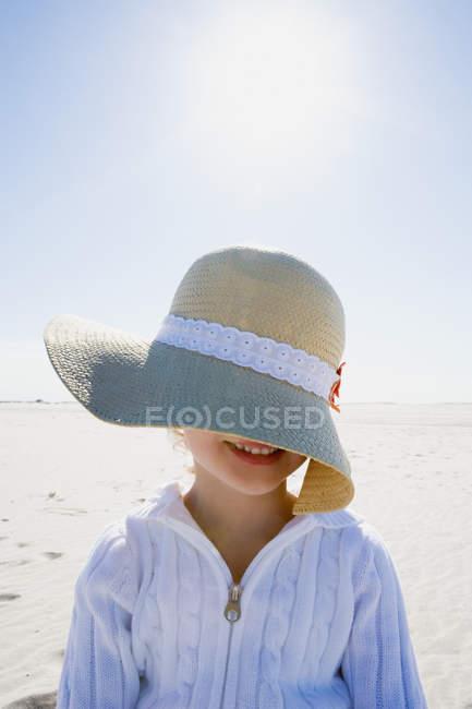 Girl wearing straw hat posing on beach — Stock Photo