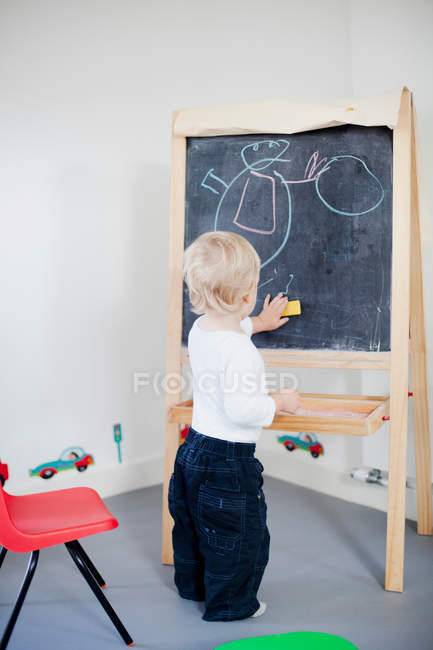 Back view of small Boy drawing on blackboard — Stock Photo