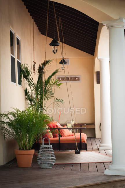 Seitenansicht der Schaukelsitz und Topfpflanzen auf Veranda — Stockfoto