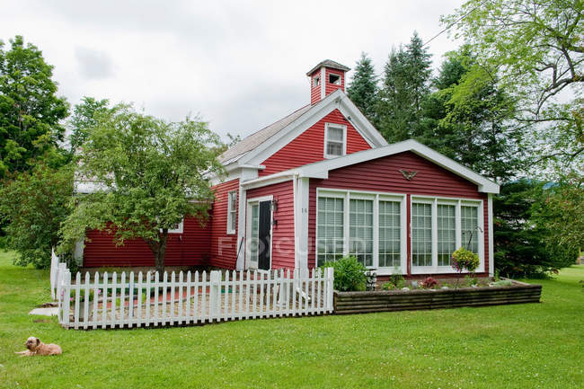 Exterior of nice red building with garden, dog lying on grass — Stock Photo