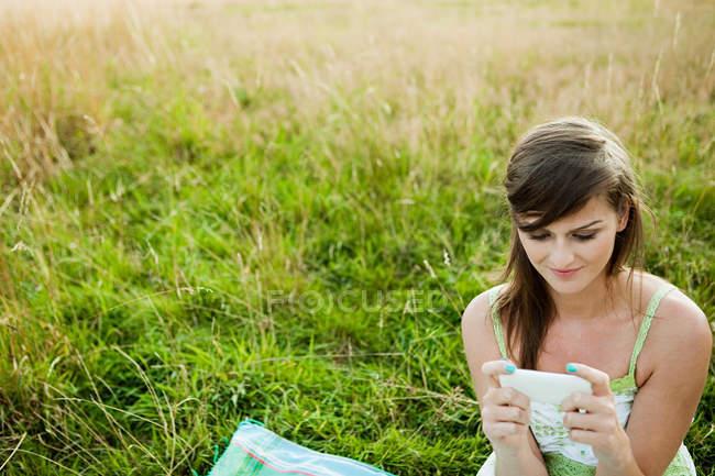 Mujer joven mirando un dispositivo de mano en un campo - foto de stock