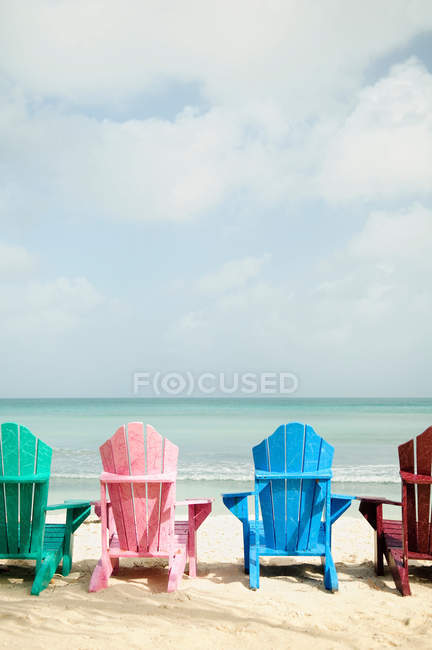 Colorful sun loungers on beach, rear view — Stock Photo