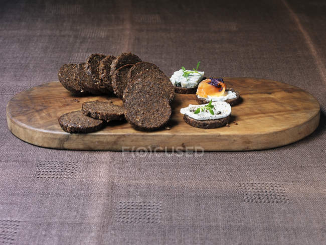 Mini pumpernickels, with cheese and salmon on wooden chopping board — Stock Photo