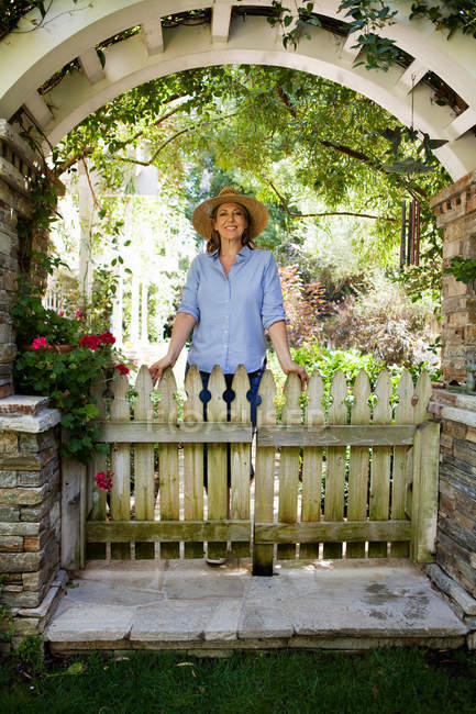 Зріла жінка, стоячи під садово-arch — стокове фото