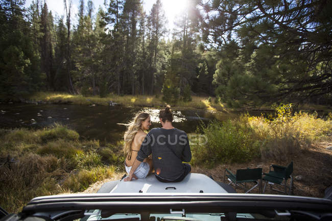 Rear view of romantic young couple sitting on jeep hood at riverside, Lake Tahoe, Nevada, USA — Stock Photo
