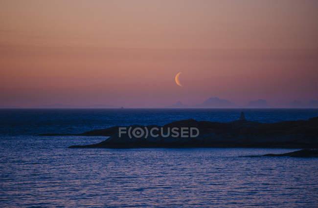 Coastline at dusk and moon on sky — Stock Photo
