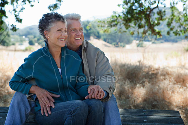 Happy couple sitting on picnic table — Stock Photo