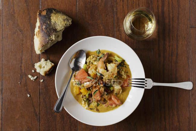 Piatto di gamberetti e granaglie con pane e bicchiere di vino in tavola — Foto stock