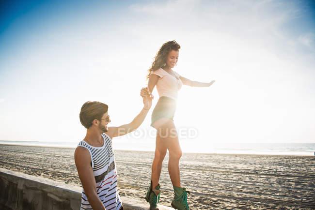 Молодая женщина, прогулки вдоль стены, бойфренд в руку для баланса — стоковое фото