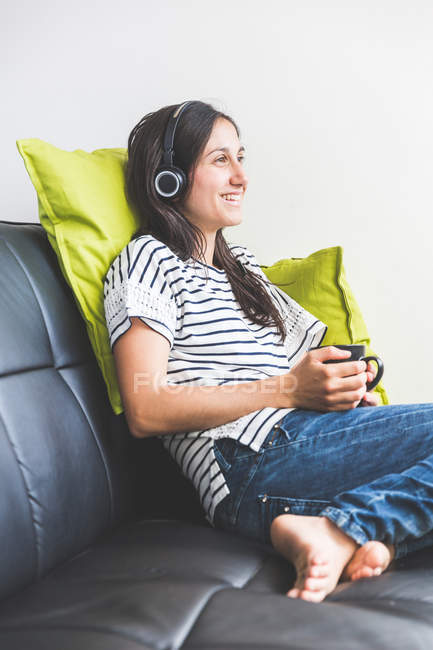Woman sitting on sofa wearing headphones holding coffee cup smiling — Stock Photo
