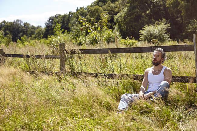 Mitte erwachsenen Mann sitzt gegen ländliche Zaun blicken — Stockfoto