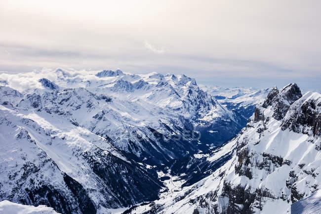 Заснеженный горный хребет под облачным небом — стоковое фото