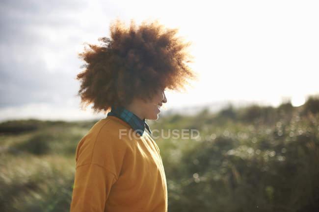 Жінка з афро волосся на трав'янистих дюн — стокове фото