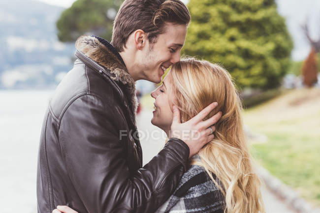 Romantique jeune homme embrasser copines front, Lac de Côme, Italie — Photo de stock