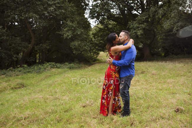 Couples mûrs à l'extérieur, restant dans le domaine, embrassant — Photo de stock