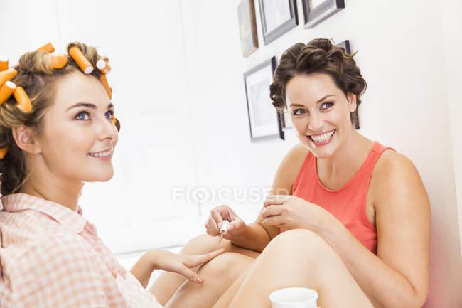 Две подруги, пенные ролики в волосах, покраска ногтей — стоковое фото