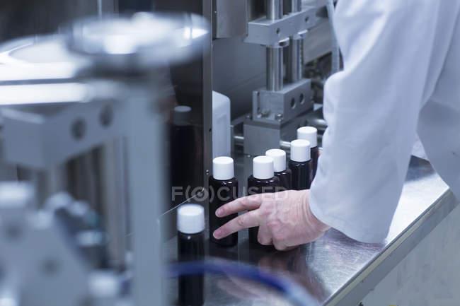Image recadrée d'un scientifique masculin chevronné avec bouteilles — Photo de stock