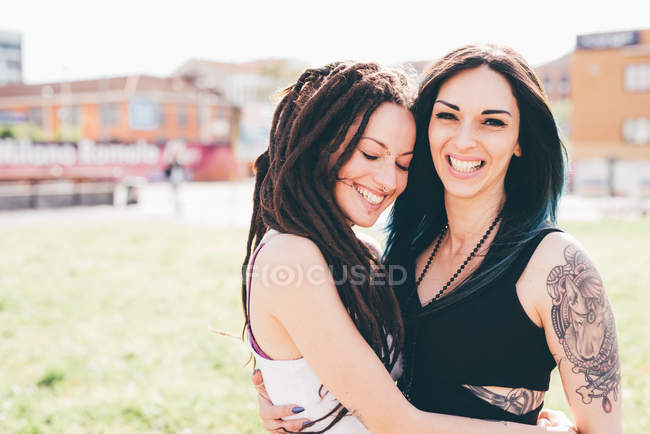 Portrait of tattooed young women in urban park — Stock Photo