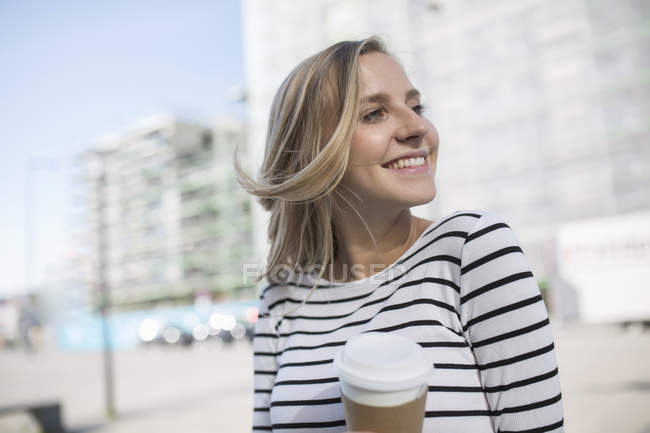 Jovem loira mulher de cabelos na cidade com takeaway café — Fotografia de Stock