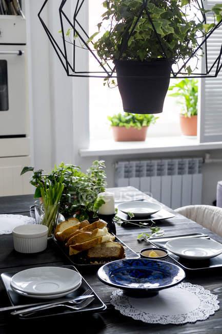 Küche Tisch mit Brotscheiben, frischen Kräutern und Frühlingszwiebeln — Stockfoto