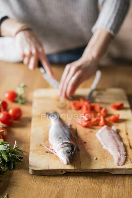 Immagine ritagliata di donna affettare pomodori al bancone della cucina — Foto stock