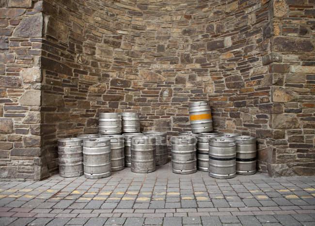 Купу порожній кеги розміщені за межами бару біля кам'яної стіни — стокове фото