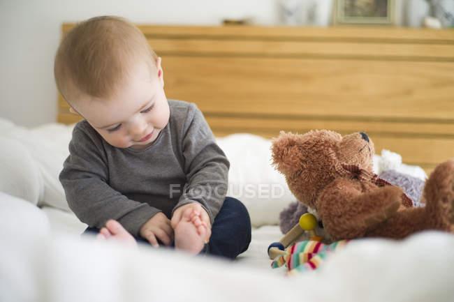 Bébé s'asseyant sur le lit enquêtant ses orteils — Photo de stock
