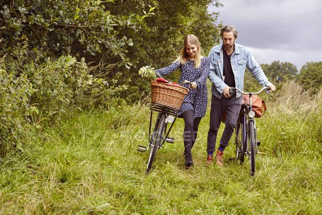 Paar Zyklen ländlichen Weg schieben — Stockfoto
