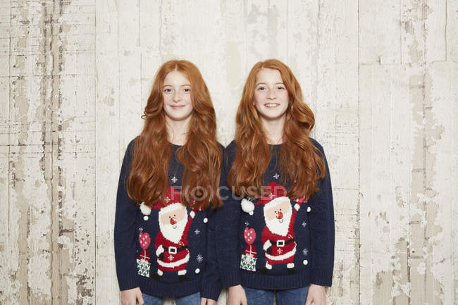 Portrait of twin sisters wearing Christmas jumpers — Stock Photo
