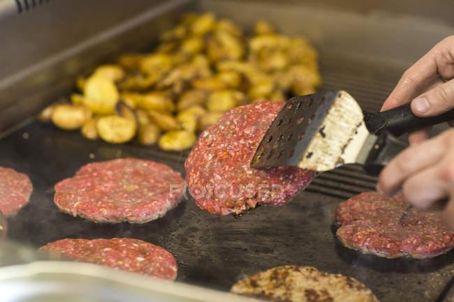 Man's hand frying burger on fast food van — стокове фото