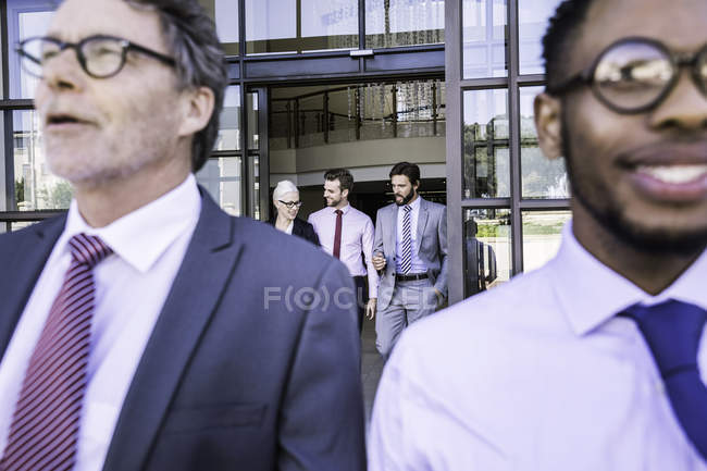 Close up of businessmen leaving office building — Stock Photo
