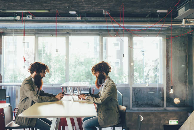 Male adult hipster twins sitting face to face at desk in office — Stock Photo