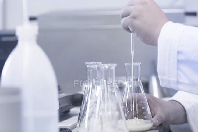 Scientist pipetting sample into beaker in laboratory — Stock Photo