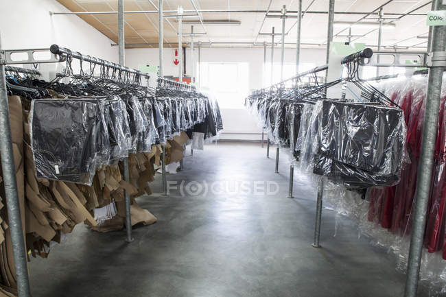 Sewing patterns and garments hanging on clothes rails in sewing factory — Stock Photo
