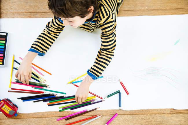 Вид зверху хлопчик лежав на підлозі, спираючись на довгий паперу — стокове фото
